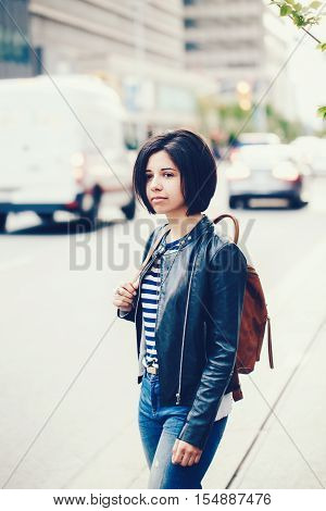 Portrait of beautiful young Caucasian latino girl woman with dark brown eyes and short dark hair in blue jeans leather biker jacket with backpack standing in street outside urban city view background
