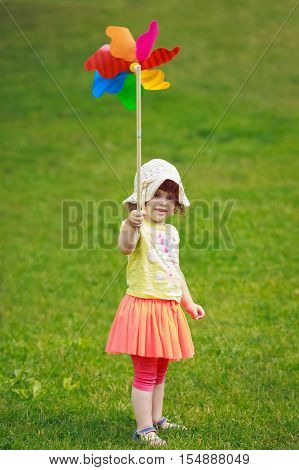 Portrait of a cute adorable little toddler girl in red skirt and summer hat holding a windmill whizzer toy in her hand standing outside in field meadow on green grass