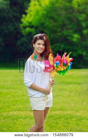 Portrait of a beautiful Caucasian young teen girl model with long hair in white shirt and pants holding windmill whizzer toys in her hands standing outside in field meadow on green grass