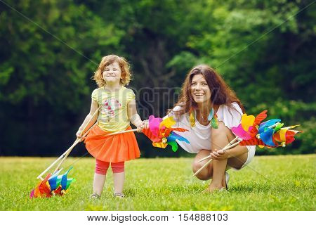 Portrait of a cute adorable little toddler girl in red skirt and her mother or sister white Caucasian females holding a windmill whizzer toy in her hand standing outside in field meadow on green grass summer fun concept