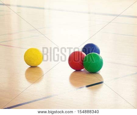 Set group of four colorful sports balls laying on the floor in gym one ball separated from others concept of individual unlike others fun activity in gym