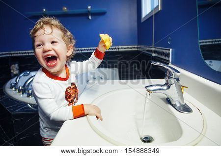 Closeup portrait of child kid toddler boy girl in bathroom toilet washing face hands playing with water lifestyle home style everyday moments morning bedtime routine