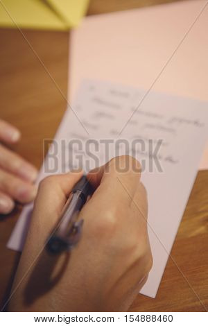 Closeup of a human female hand holding pen and writing letter or text on paper on the background selective focus shallow depth of field toned with filters
