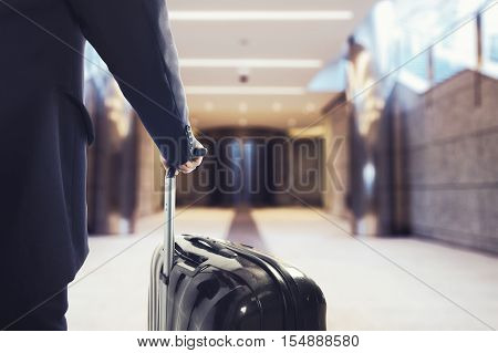 Businessman walking in the airport with suitcase