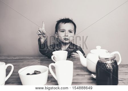 Close-up black and white candid natural portrait of cute adorable little boy toddler in kitchen indoors making funny face lifestyle documentary style grainy film effect