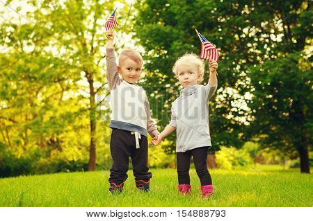 Happy adorable little blond Caucasian girl and boy smiling laughing holding hands and waving American flag outside celebrating 4th july Independence Day Flag Day concept