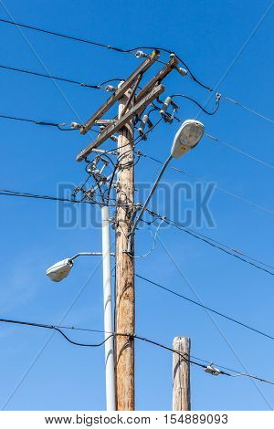A street light pole with electricity line and blue sky background.