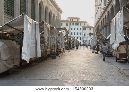 Florence, Italy-June 13, 2015. Stall holder in the early morning at the famous San Lorenzo outdoor leather market during the  set up of the market stalls