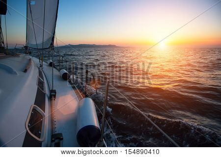 Yacht sailing against sunset. Luxury boat. Vacation and Travel Concept.