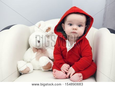 Portrait of cute adorable Caucasian smiling sad baby boy girl with black brown eyes in red hoodie shirt sitting in chair with toy looking directly in camera