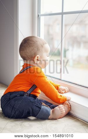 Portrait of cute adorable Caucasian baby boy with black eyes in orange shirt onesie jeans with suspenders barefoot sitting on windowsill looking away natural window light lifestyle