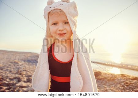 Portrait of cute adorable happy smiling toddler little girl with towel on beach making poses faces having fun emotional face expression lifestyle sunset summer mood toned