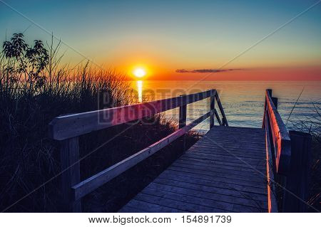 Beautiful evening sunset landscape at Canadian Ontario lake Huron in Pinery Park orange blue red sky sun. Amazing summer sunset view on the beach. Dunes grass wooden stair leading to water