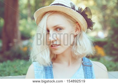Portrait of beautiful Caucasian teenage young blonde alternative model girl woman with light grey blue eyes in straw hat with bow looking in camera toned with Instagram filters