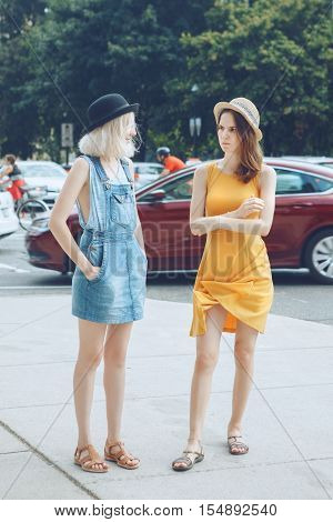 Portrait of two white Caucasian unformal young girls hipster students teenagers friends in dresses hats outside standing talking in urban city street crowded with cars
