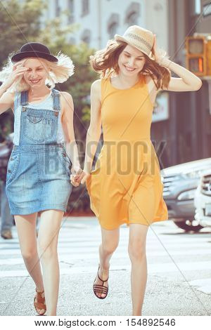 Portrait of two white Caucasian unformal young girls hipster students teenagers friends in dresses hats outside running crossing urban city street crowded with cars best friends forever
