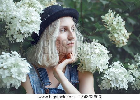 Closeup portrait of beautiful Caucasian teenage young blonde alternative model girl woman in blue tshirt jeans romper black hat sitting among large white flowers on summer day