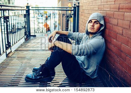 Conceptual art portrait of beautiful handsome young middle east brunette man with beard wearing grey hoodie sitting on staircase outside in city looking away