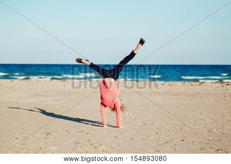 Portrait of funny white Caucasian child kid teenager doing cartwheel playing on beach on sunset autumn fall season happy lifestyle childhood concept