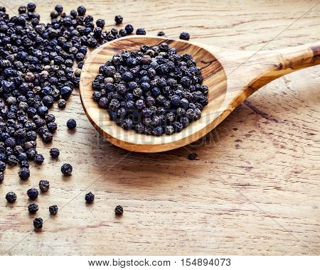 Closeup Black Pepper In Wooden Spoon On Shabby Teak Wood Table. Seasoning And Species Ingredients Co