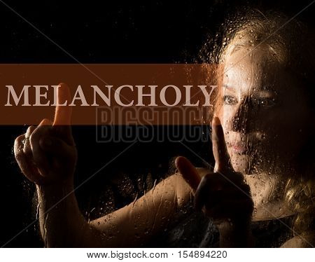 melancholy written on virtual screen. hand of young woman melancholy and sad at the window in the rain.