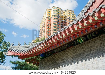 Cornice of traditional chinese roof and part of contemporary building. Colorful clay roof on background of high-rise building.
