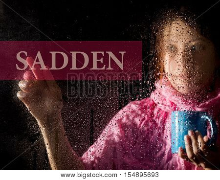 sadden written on virtual screen. young woman melancholy and sad at the window in the rain, she holding a cup of hot coffee or tea.