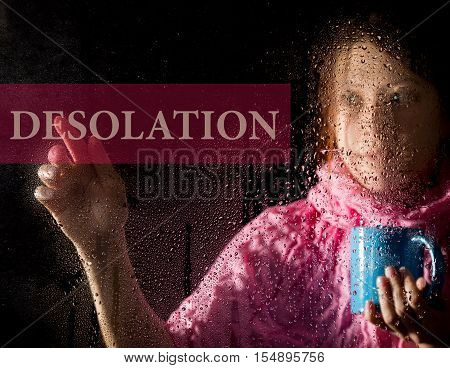 desolation written on virtual screen. young woman melancholy and sad at the window in the rain, she holding a cup of hot coffee or tea.