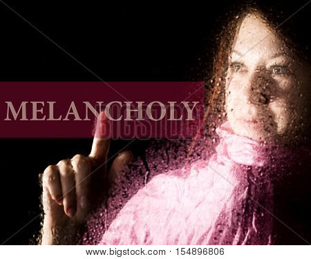 melancholy written on virtual screen. young woman melancholy and sad at the window in the rain, her neck warm scarf.