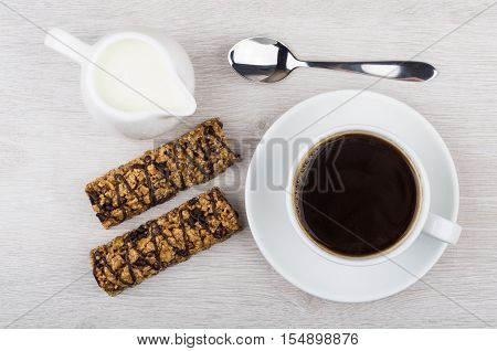 Black Coffee, Cereal Bars And Jug Of Milk On Table