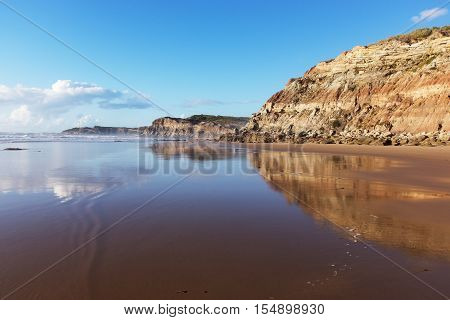 Mountain reflected in the smooth water of the beach Areia Branca. Lourinha, West coast of Portugal