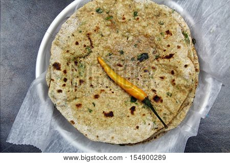 Overhead view of a stack of whole wheat and chopped spinach leaves Chapati or Roti or Tortilla with a hot chili pepper