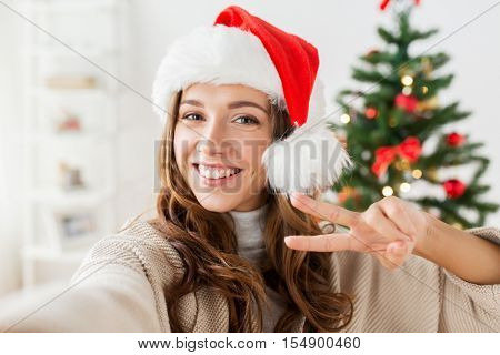 holidays, winter and people concept - happy young woman in santa hat taking selfie over christmas tree at home