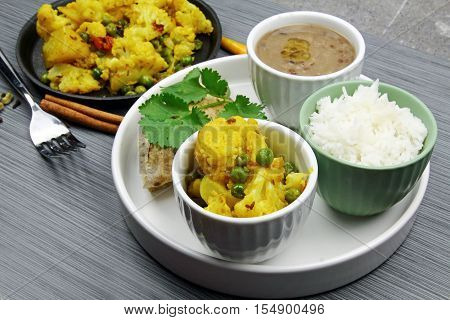 A platter with cauliflower dry curry urad daal or brown lentils rice and chapati selective focus.