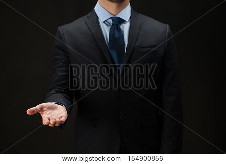 business, virtual reality, people, technology, cyberspace and office concept - close up of businessman in suit holding something imaginary on palm of his hand