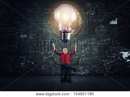 Kid sitting on chair with his arms raised to a lightbulb in a dark classroom with a blackboard full of math formulas.
