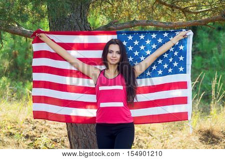 Beautiful model poses with the flag of the United States in the summer park