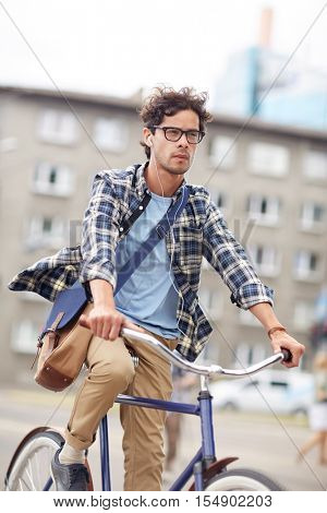 people, style, leisure and lifestyle - young hipster man with shoulder bag and earphones riding fixed gear bike on city street