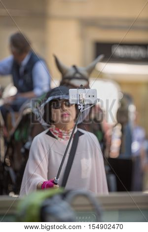 Florence Italy-June 2 2015. Asian female tourist using a selfie stick to take a photo of herself on her mobile phone in Florence Italy