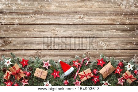 Fir tree branches with advent calendar stars and gift boxes on old wooden board