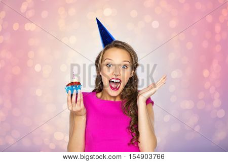 people, holidays, emotion, expression and celebration concept - happy young woman or teen girl in pink dress and party cap with birthday cupcake over rose quartz and serenity lights background