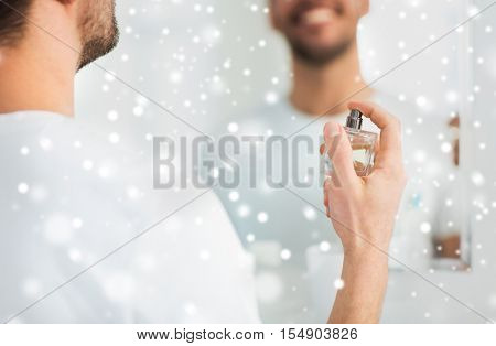 perfumery, beauty and people concept - close up of happy smiling young man with perfume looking to mirror using scent at bathroom over snow