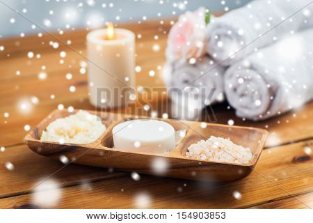 beauty, spa, bodycare, natural cosmetics and bath concept - soap natural cosmetics himalayan salt and scrub in wooden bowl on table over snow
