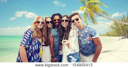summer vacation, travel, tourism, technology and people concept - smiling young hippie friends taking picture by smartphone selfie stick over beach background