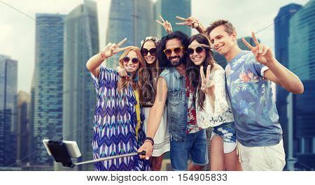 summer vacation, travel, tourism, technology and people concept - smiling young hippie friends taking picture by smartphone selfie stick over singapore city street background