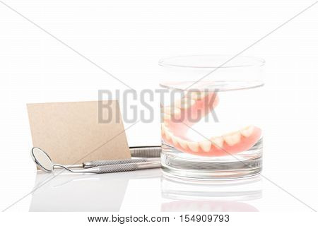 Close up of dentures in glass of water and dental tool with notice paper on white backgrounda