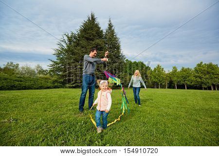 Happy Family.mother, Father, Children  Running Over A Green Meadow. Fly A Colorful Kite.