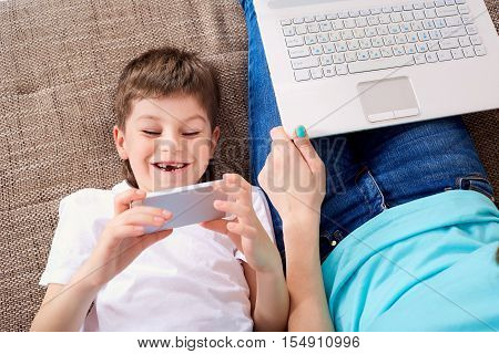 Boy Looks At The Phone.mother With Laptop. Top View.