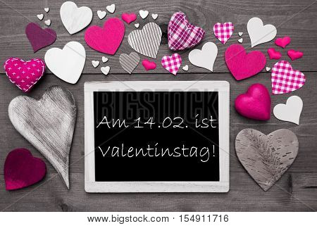 Chalkboard With German Text Valentinstag Means Valentines Day. Many Pink Textile Hearts. Grey Wooden Background With Vintage, Rustic Or Retro Style. Black And White Style With Colored Hot Spots