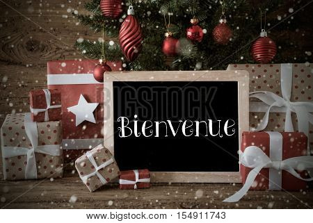 Nostalgic Christmas Card For Seasons Greetings. Christmas Tree With Balls And Snowflakes. Gifts Or Presents In The Front Of Wooden Background. Chalkboard With French Text Bienvenue Means Welcome